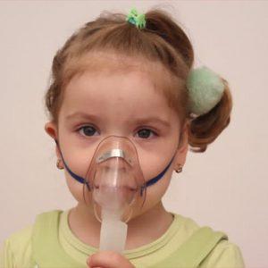 Ребенок дышит через маску небулайзера