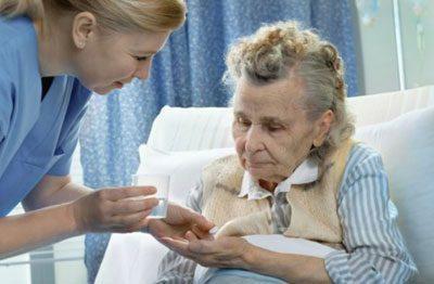 Медсестра дает больному таблетки