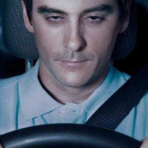Уставший человек за рулем