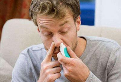 Парень капает нос назонексом