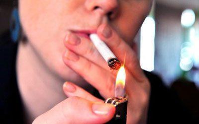 Женщина прикуривает сигарету