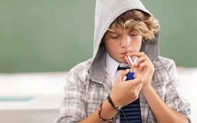 Парень прикуривает сигарету